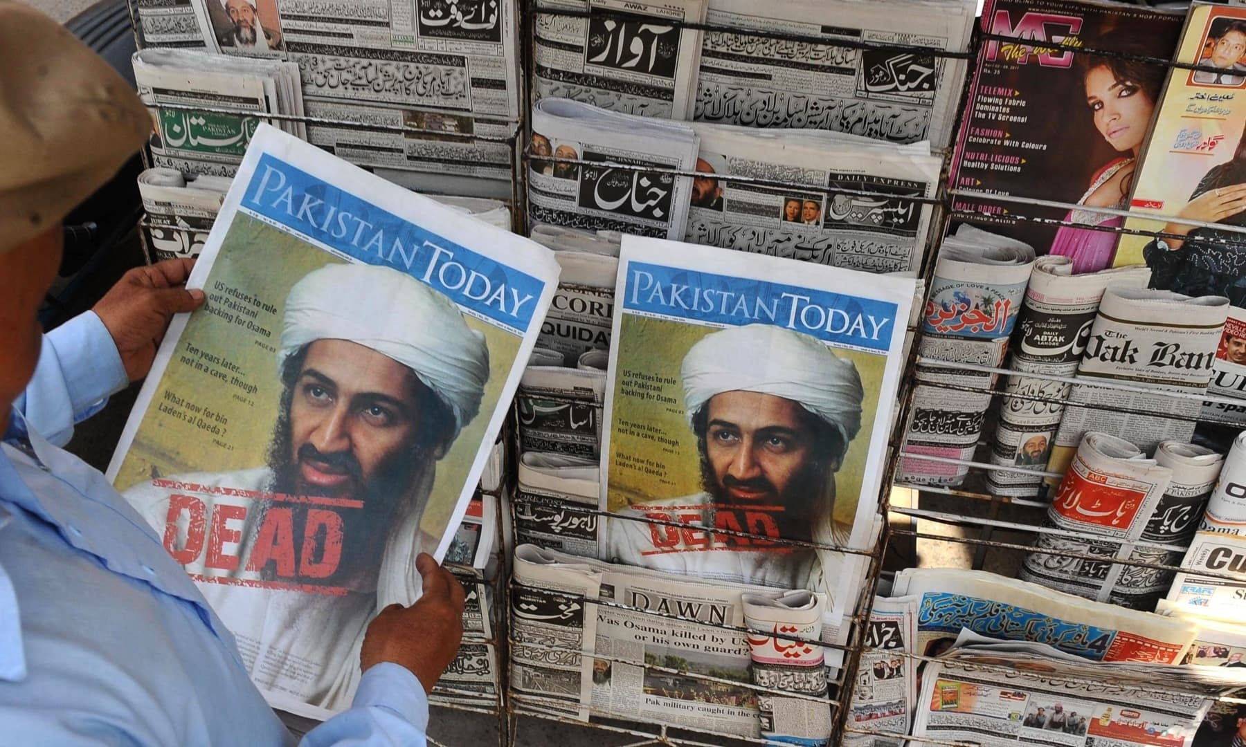 In this file photograph taken on May 3, 2011, a man reads a newspaper with the front page displaying news of the death of Osama bin Laden at a stall in Lahore. — AFP