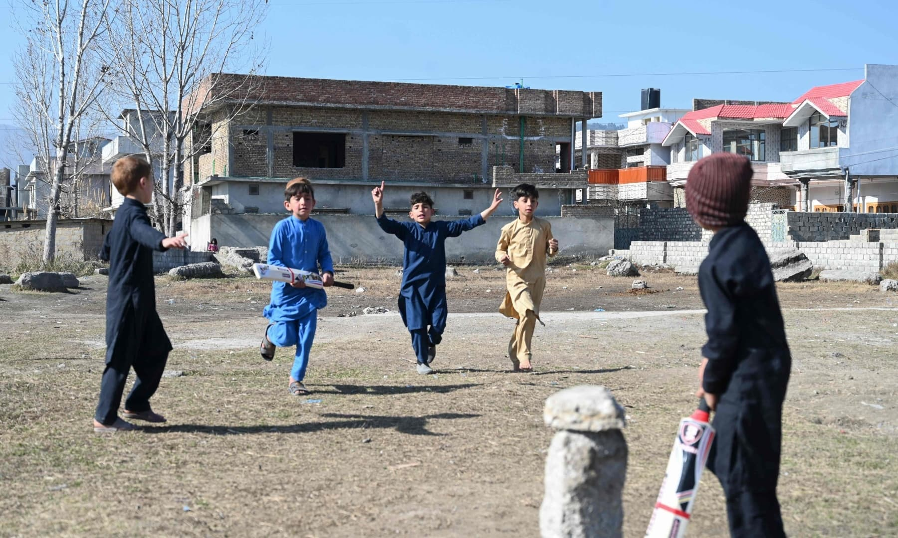 Children play cricket at the site of the demolished compound of Osama bin Laden in northern Abbottabad, in this picture taken on February 11, 2021. — AFP