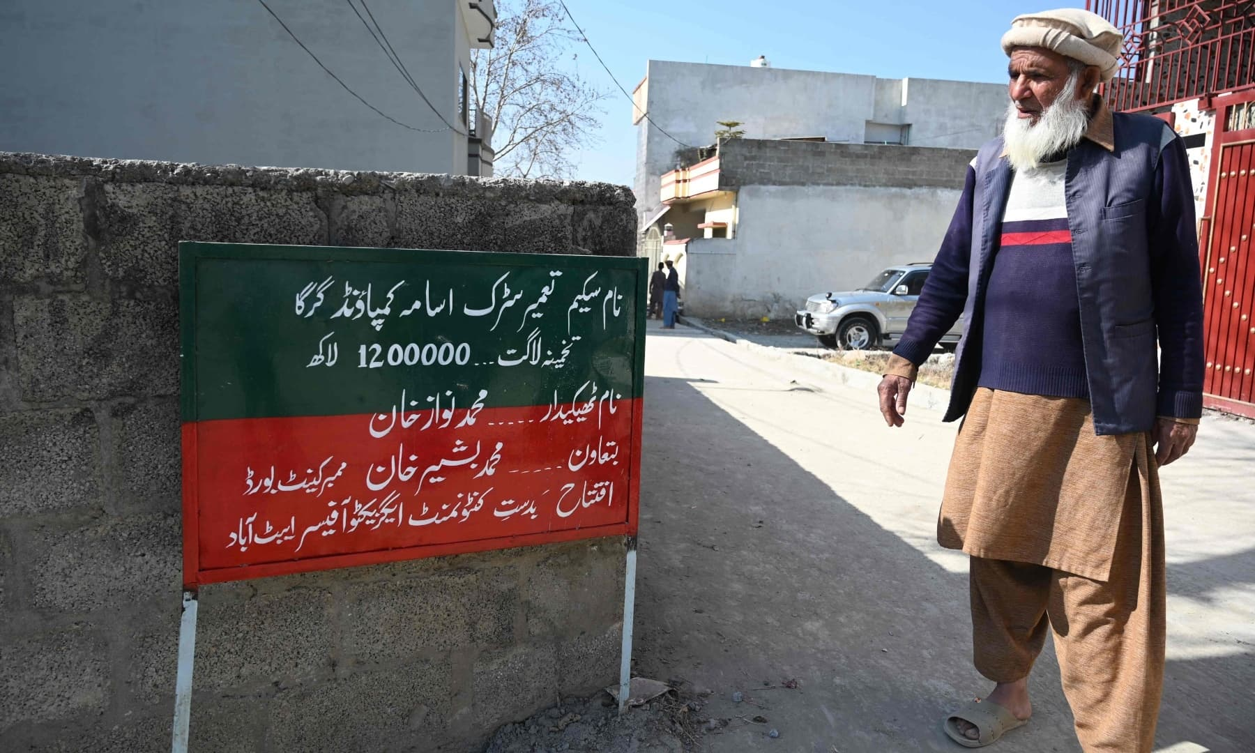 Local resident Altaf Hussain and neighbour of Osama bin Laden stands next to a signboard at the site of the demolished compound of Bin Laden in northern Abbottabad, in this picture taken on February 11, 2021. — AFP