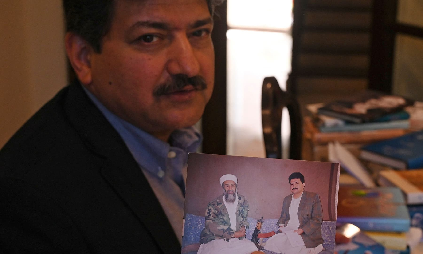 Prominent journalist Hamid Mir shows his photograph with Osama Bin Laden, when he interviewed him at an undisclosed location in Afghanisnan in the 1990s, during an interview with AFP in Islamabad on April 27, 2021. — AFP