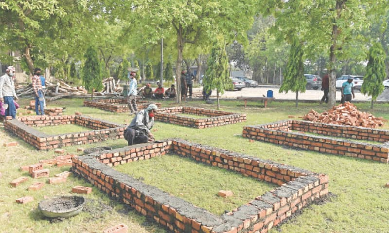 NEW DELHI: Workers are building makeshift platforms for funeral pyres on the premises of a crematorium on Tuesday.—AFP