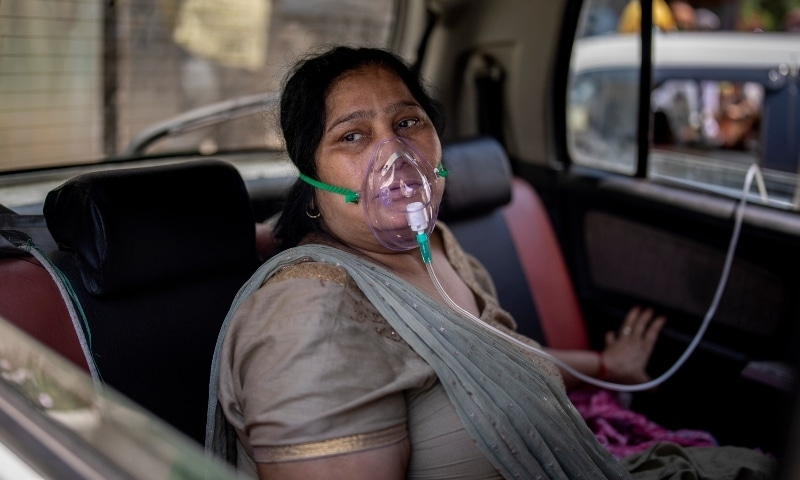 In this file photo, a Covid-19 patient sits inside a car and breathes with the help of oxygen provided by a Gurdwara in New Delhi. — AP