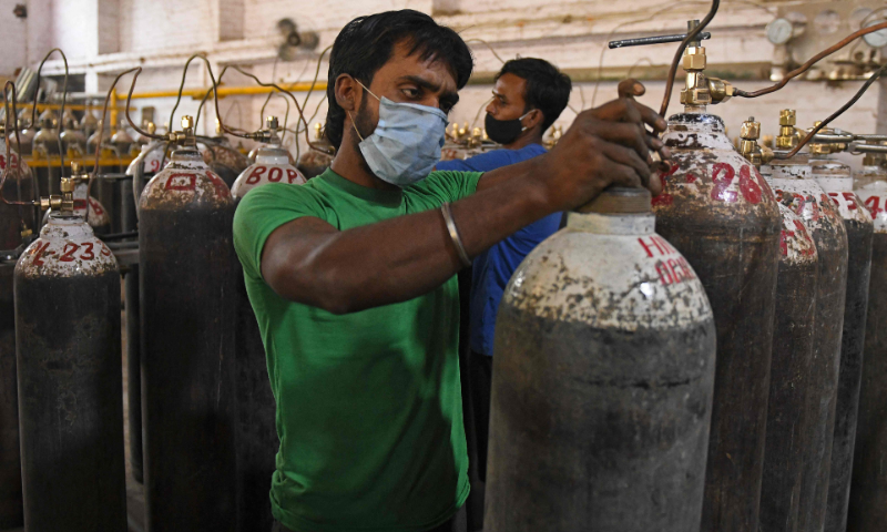 Workers are seen sorting oxygen cylinders that are being used for Covid-19 patients before dispatching them to hospitals at a facility on the outskirts of Amritsar, India on Wednesday. — AFP