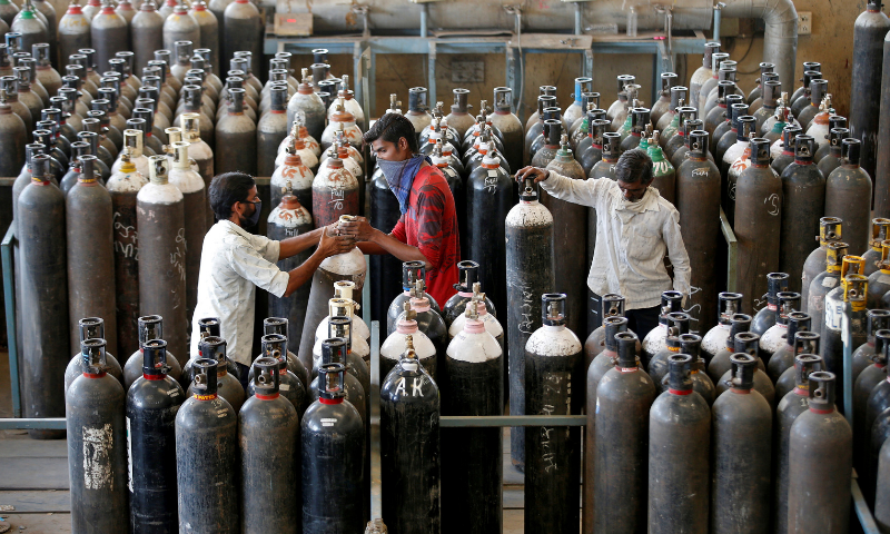 People carry oxygen cylinders after refilling them in a factory, amidst the spread of the coronavirus in Ahmedabad, India on April 25. — Reuters