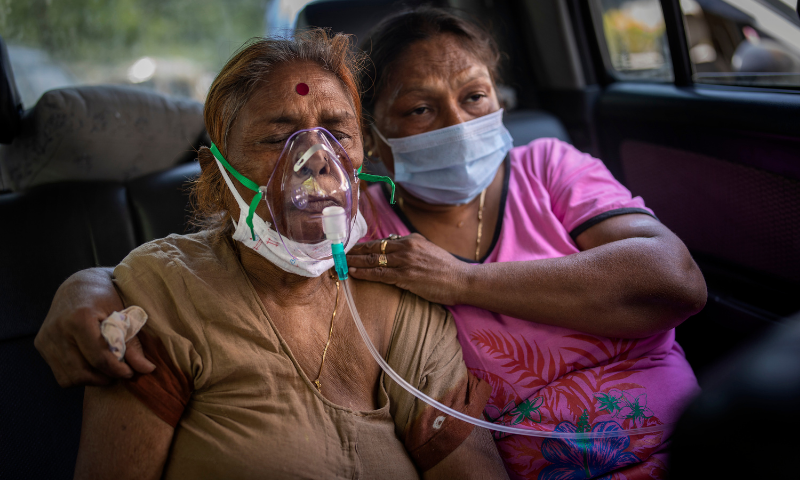 A Covid-19 patient inside a car, receives oxygen provided by a Gurdwara in New Delhi, India on April 24. — AP