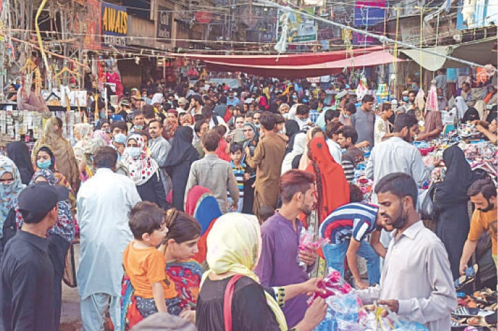 SHOPPERS throw caution to the wind without wearing face masks or observing social-distancing as they move shoulder to shoulder in this street market in famous Shahi Bazaar  in Hyderabad on Wednesday.—Dawn
