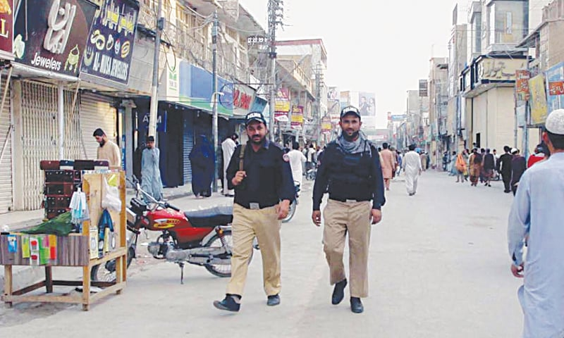 QUETTA: Two policemen patrol a market during the smart lockdown imposed in the area due to increasing Covid-19 cases on Wednesday.—INP