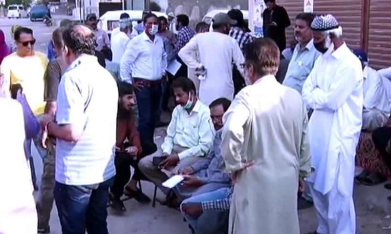 People gather outside a polling station on Thursday. — DawnNewsTV