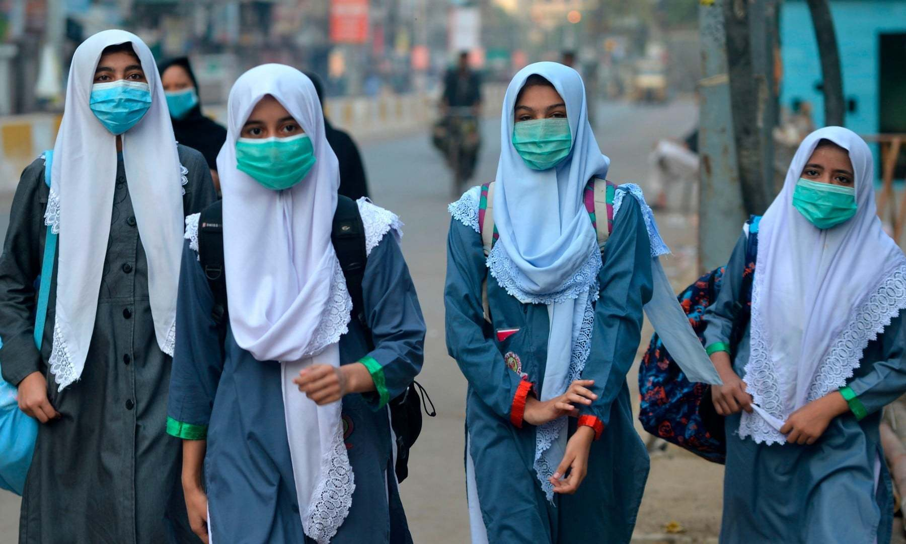 Students wearing face masks walk through a street to their school in Karachi on September 15. — AFP