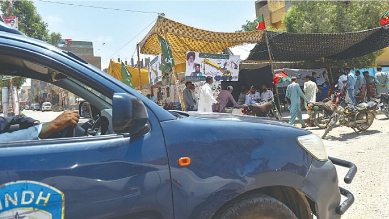 A police vehicle stands by as voters approach polling camps set up by different parties in the constituency on Thursday.—Fahim Siddiqi/White Star