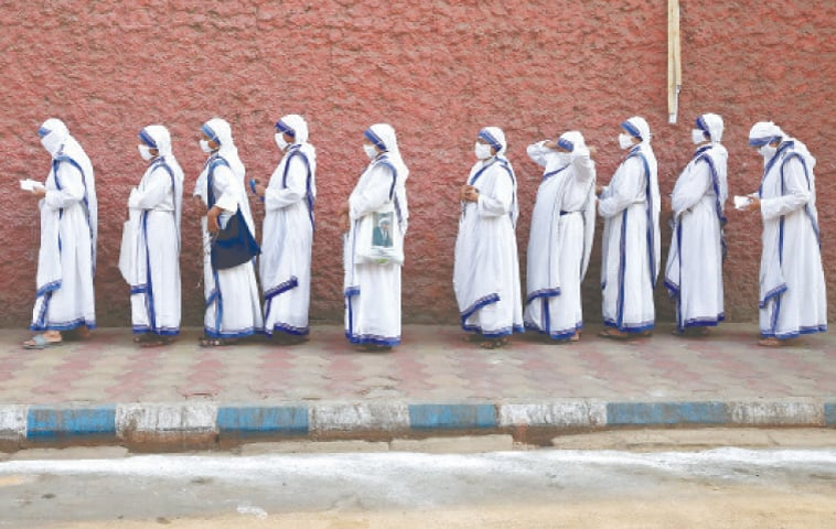 NUNS from the Missionaries of Charity, the global order founded by Mother Teresa, wait in a line to cast their vote outside a polling station in Kolkata.—Reuters