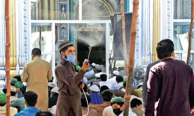 A man sprays sanitiser on people offering prayers at Jamia Mosque in Rawalpindi on Friday. — Online