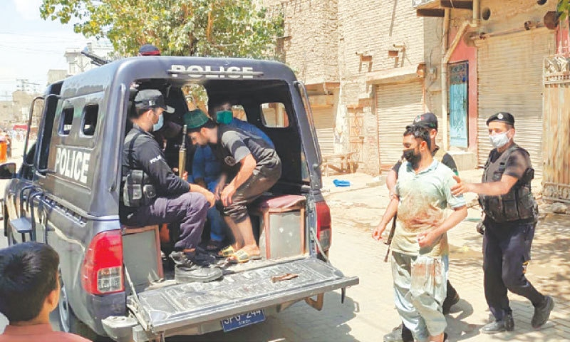 A SHOPKEEPER is picked up by police in Larkana during a drive against violators of SOPs on Friday.—PPI