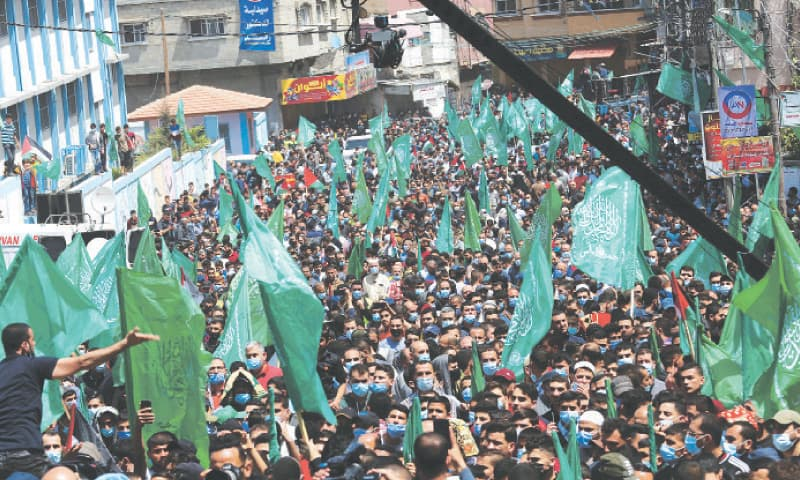 GAZA CITY: Hamas supporters wave flags during a rally on Friday against the Palestinian president's decision to postpone elections. — AP