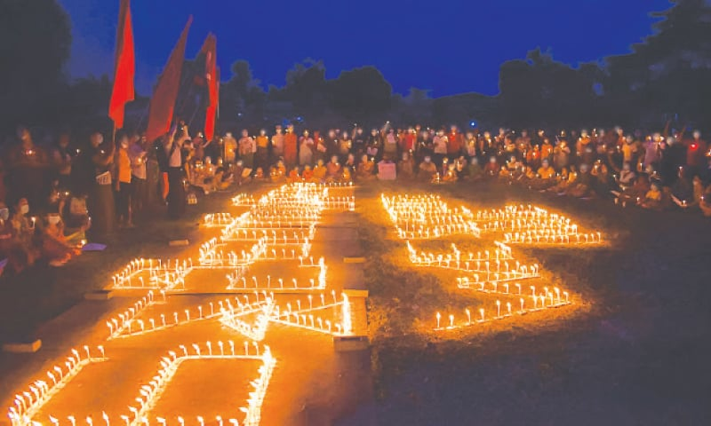 MOHNYIN: People take part in a candle light protest during a demonstration against the military coup. — AFP
