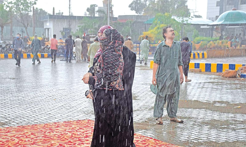 PEOPLE enjoy showers in otherwise hot weather conditions in a Hyderabad locality on Saturday. — Dawn