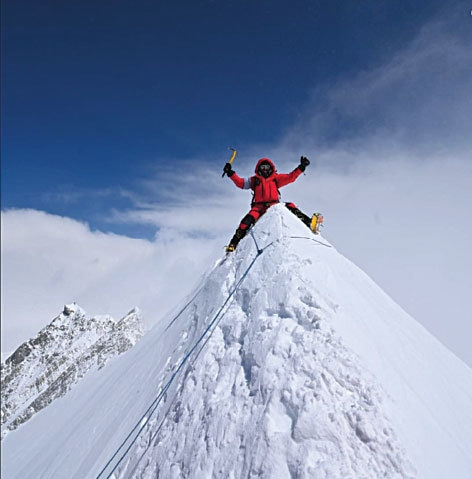 Sirbaz Khan raising his arms in victory on top of Annapurna