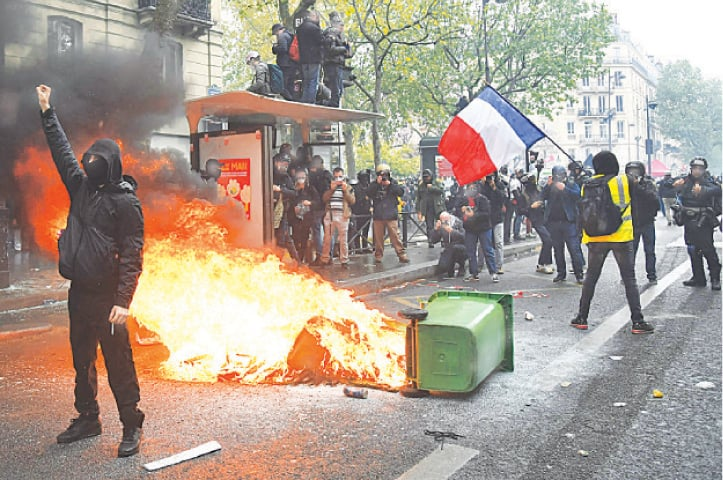 PARIS: Protesters stand near a burning trash bin during a rally on Saturday. Hooded, black-clad demonstrators clashed with the police as thousands of people joined traditional May Day protests across France to demand social and economic justice. Marchers, most wearing masks in line with coronavirus rules, carried banners one of which read, 'We want to live, not survive'. — AFP