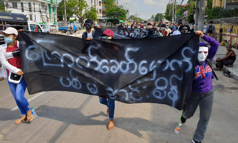Protesters hold banners during a demonstration against the military coup in Yangon's Insein township on Saturday. — AFP