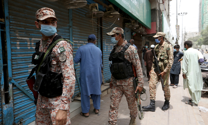 Army and paramilitary soldiers patrol at a market to enforce new restrictions announced to help control the spread of the coronavirus on Saturday. — AP