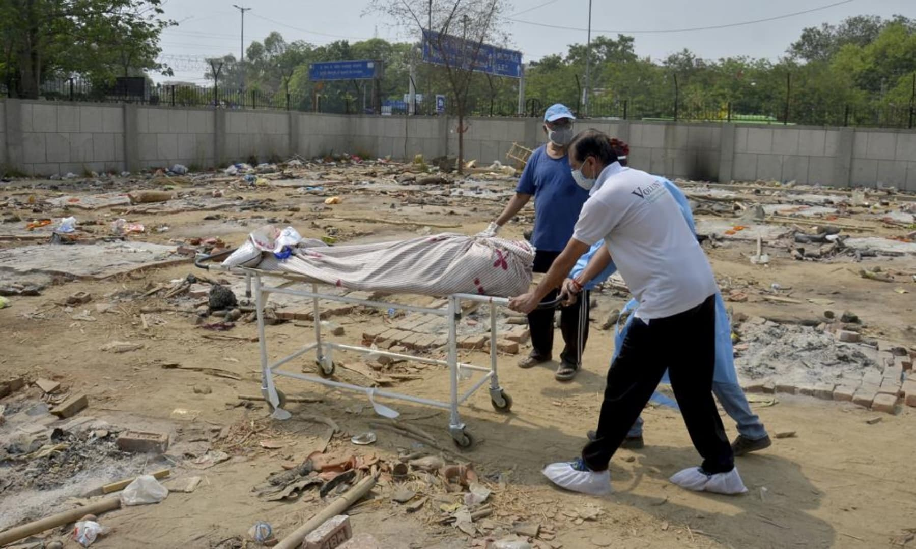 The body of a Covid-19 victim is wheeled in a ground that has been converted into a crematorium in New Delhi, India, May 1, 2021. — AP