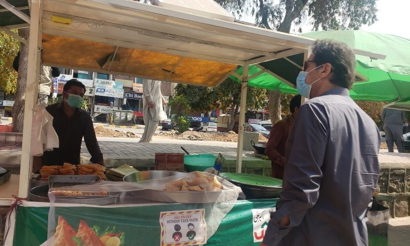 Prime Minister Imran Khan talks to a vendor selling snacks in Islamabad on Sunday. — Photo: Senator Faisal Javed Khan Twitter