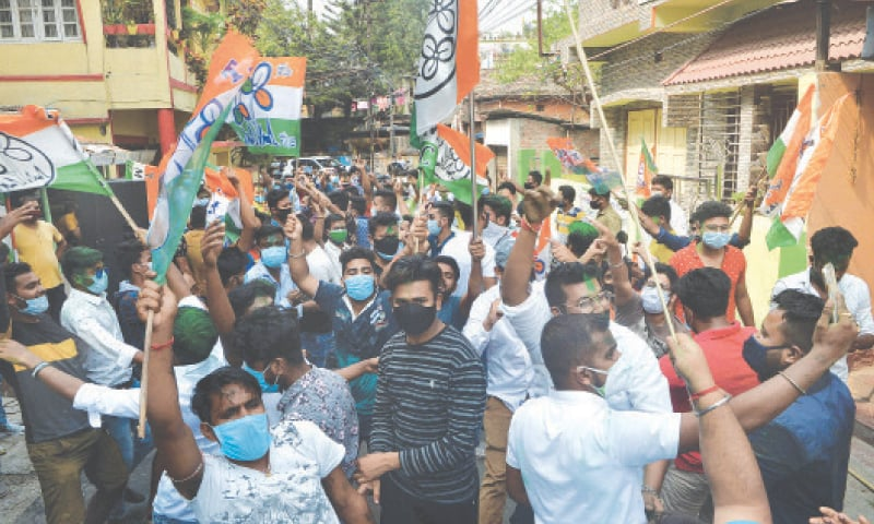 SILIGURI: Supporters of the All India Trinamool Congress celebrate the party's lead in elections to West Bengal's legislative assembly on Sunday.—AFP