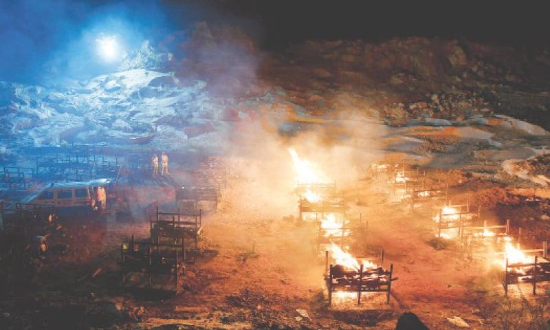 BENGALURU: Volunteers stand beside burning pyres of people who died of the coronavirus disease at a crematorium ground in a village in Karnataka state.—Reuters