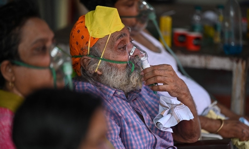 Patients breathe with the help of oxygen provided by a Gurdwara, a place of worship for Sikhs, under a tent installed along the roadside in Ghaziabad on May 2. — AFP