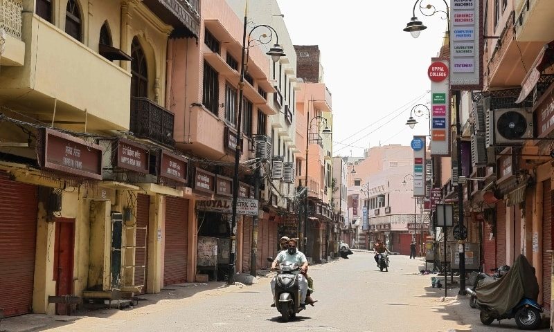 Motorists ride through a closed market area during the weekend lockdown imposed by the state government in Amritsar on May 2. — AFP