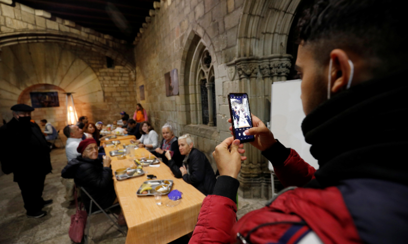 A man takes a picture with a mobile during a charity Ramazan dinner in the cloister at Santa Anna church. — Reuters