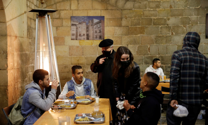 Priest Peio Sanchez speaks with people during a charity Ramazan dinner in the cloister at Santa Anna church during the coronavirus outbreak in Barcelona, Spain on April 28. — Reuters