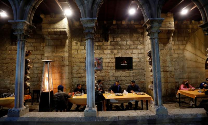 People eat during a charity Ramazan dinner in the cloister at Santa Anna church during the coronavirus outbreak, in Barcelona, Spain on April 28. — Reuters