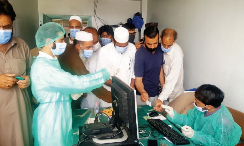 People ignore SOPs before getting coronavirus jabs at King Abdullah Teaching Hospital, Mansehra, on Monday. — Dawn