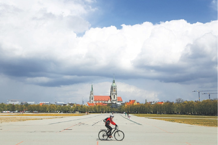 A CYCLIST crosses the Oktoberfest beer festival area in front of St. Paul's church in Munich.—AP
