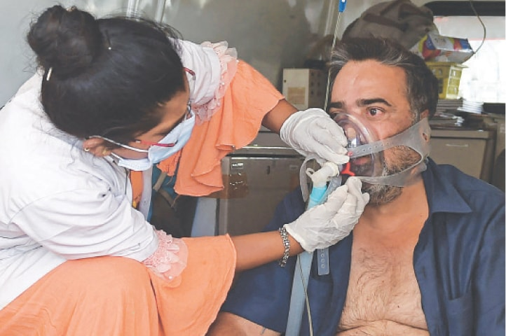 AHMEDABAD: A Covid-19 patient on oxygen support is helped by a health worker inside an ambulance while waiting for admission in a hospital on Monday. India's total Covid-19 caseload neared 20 million and oxygen shortages exacerbated a devastating second wave.—AFP