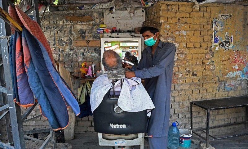 A barber wearing a facemask attends a customer at his roadside stall in Rawalpindi on May 3. — AFP
