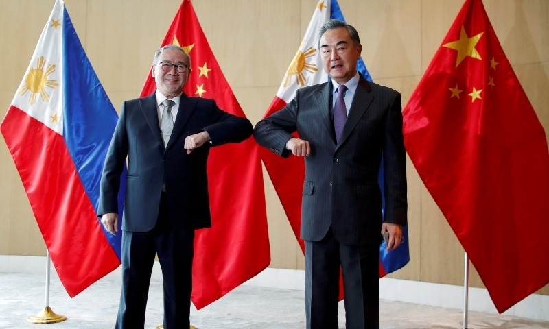 China's Foreign Minister Wang Yi and Philippine's Foreign Affairs Secretary Teodoro Locsin Jr., bump their elbows during a meeting in Manila on Jan 16. — Reuters