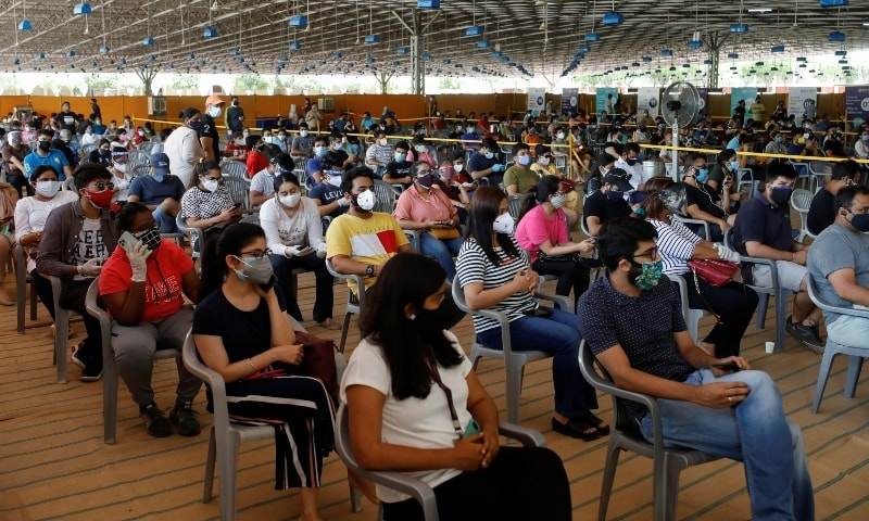 People wearing protective face masks wait to receive a dose of COVISHIELD, a vaccine manufactured by Serum Institute of India, at a vaccination centre in New Delhi on May 4. — Reuters