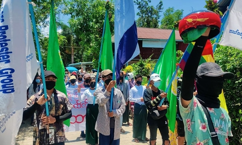 This handout photo taken and released by Dawei Watch on May 3 shows a protester holding an overturned alms bowl as others hold flags during a demonstration against the military coup in Dawei. — AFP