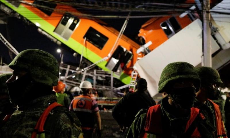 پُل ٹوٹنے کے باعث ٹرین کا کچھ حصہ زمین پر آگرا جبکہ باقی تاروں کے ساتھ لٹک گیا — فوٹو: رائٹرز