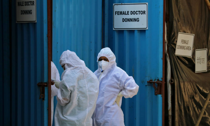 Healthcare workers wearing personal protective equipment (PPE) stand outside a donning area at a Covid-19 care facility in Mumbai, India on Tuesday. — Reuters