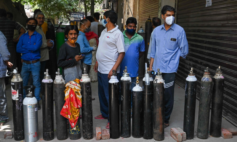 People wait to refill their medical oxygen cylinders for Covid-19 patients under home quarantine at a private refill centre in New Delhi on Tuesday. — AFP