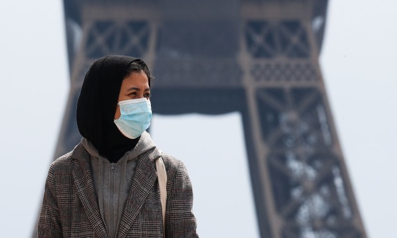 A woman, wearing a hijab and a protective face mask, walks at Trocadero square near the Eiffel Tower in Paris, France, May 2, 2021. — Reuters