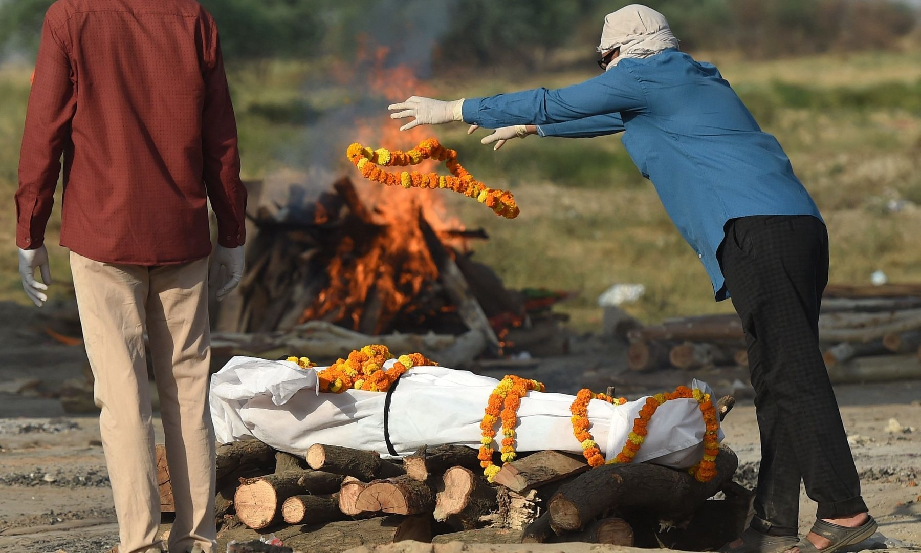 Relatives perform the last rites before the cremation of their loved one who died due to Covid-19 at a cremation ground in Allahabad, India on May 4. — AFP
