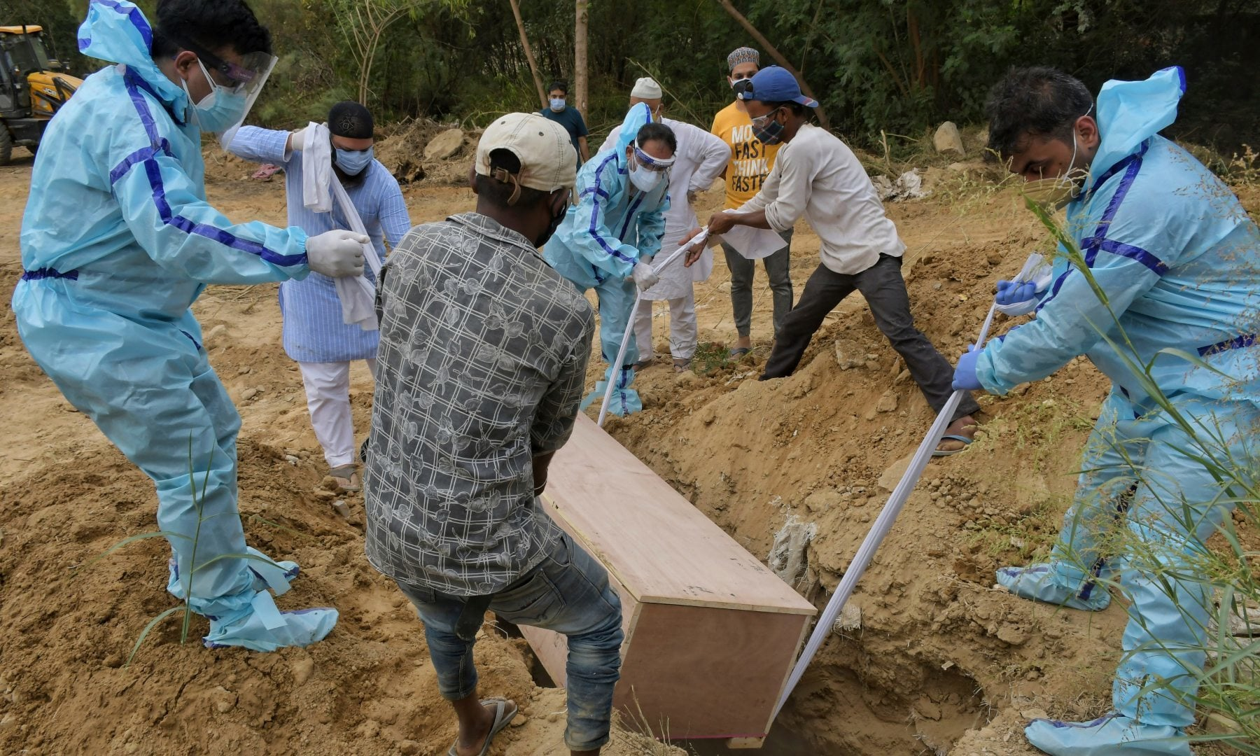 Relatives bury the body of a Covid-19 victim at a graveyard in New Delhi, India, Tuesday, May 4. — AP