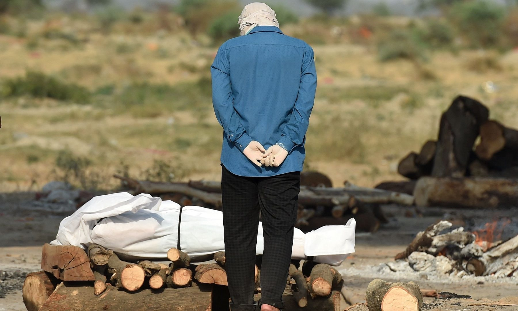 A relative mourns next to the body of his loved one who died due to Covid-19 at a cremation ground in Allahabad on May 4. — AFP