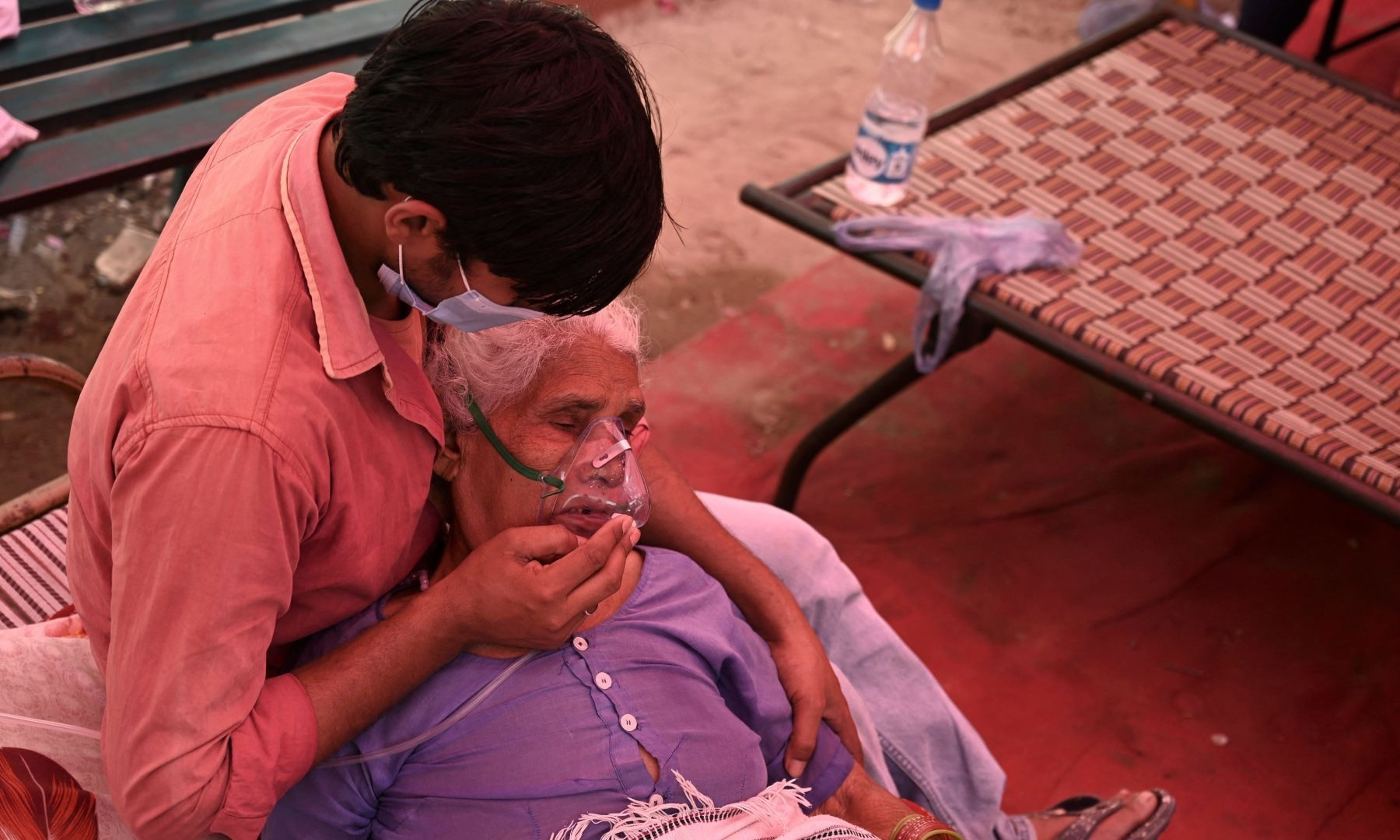 A family member comforts a patient breathing with the help of oxygen being provided by a Gurdwara, a place of worship for Sikhs, under a tent installed along the roadside amid Covid-19 pandemic in Ghaziabad on May 4. — AFP