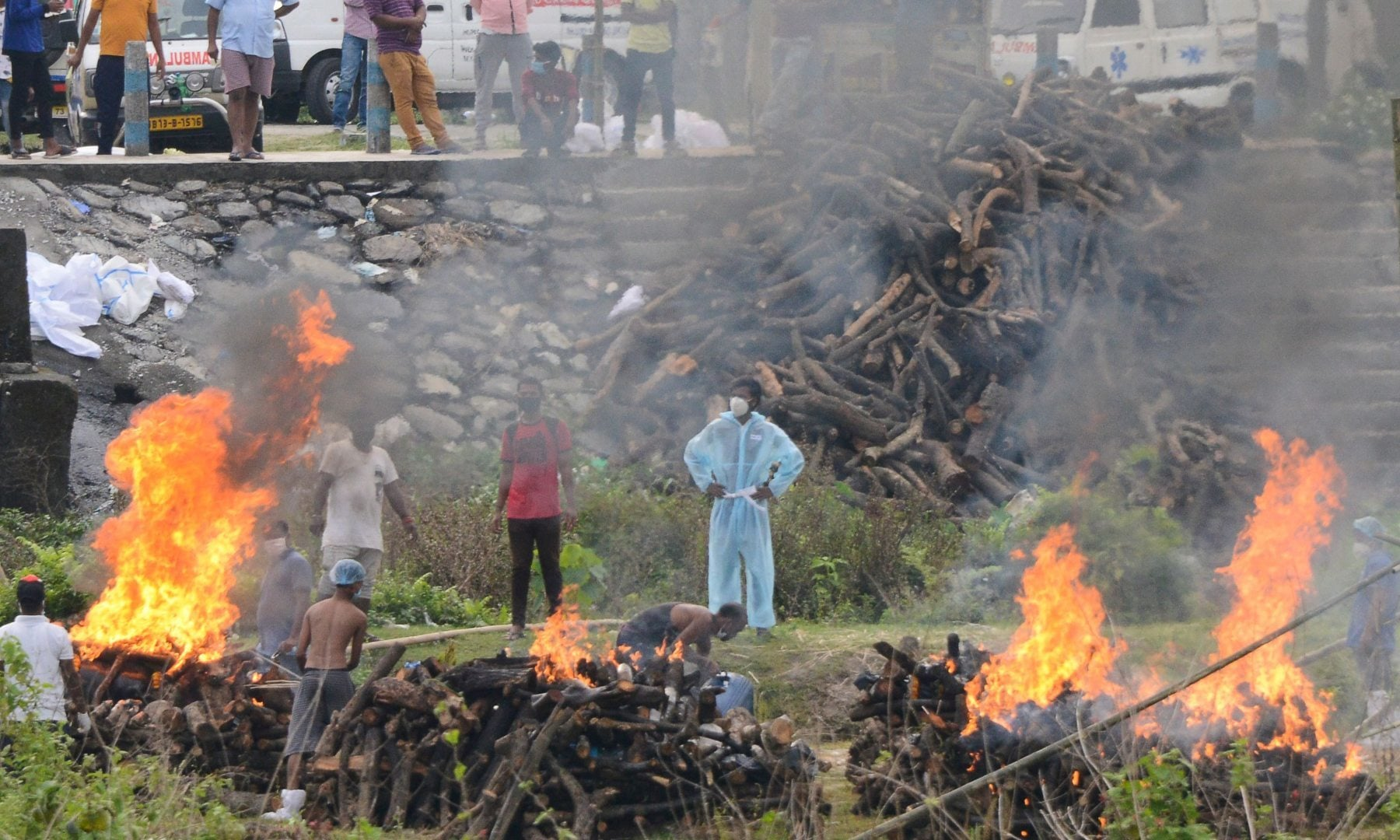 People watch the cremation of people who died due to the coronavirus at Sahudangi Crematorium, some 15km from Siliguri, India on May 4. — AFP