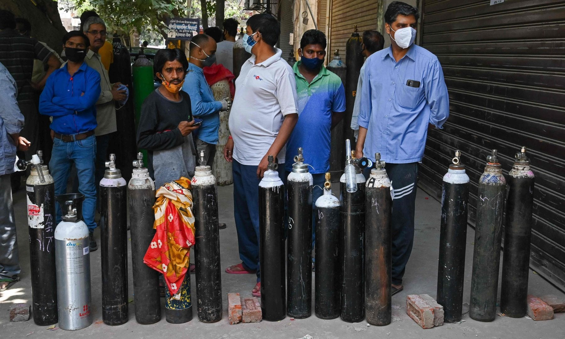 People wait to refill their medical oxygen cylinders for Covid-19 patients under home quarantine at a private refill centre in New Delhi on May 4. — AFP